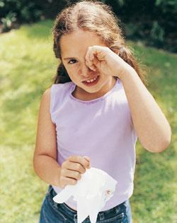 girl rubbing her left eye